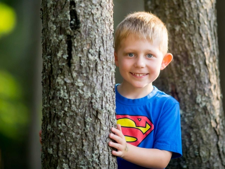 boy hiding behind tree smiling
